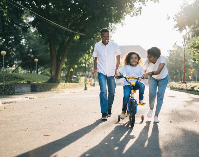 parents helping kid ride bike