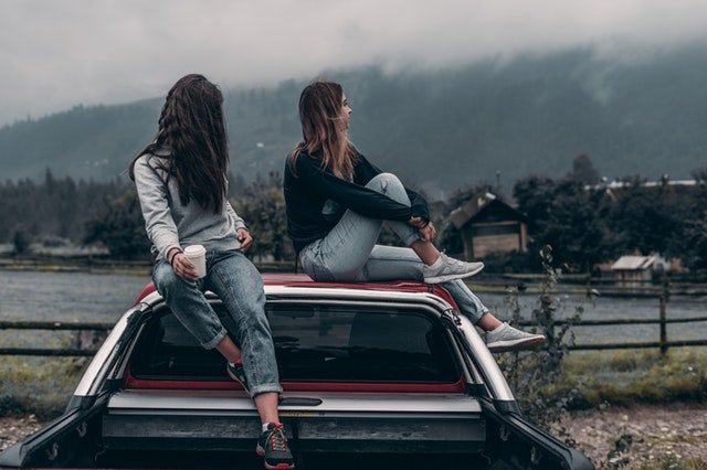 Two women sitting on a vehicle